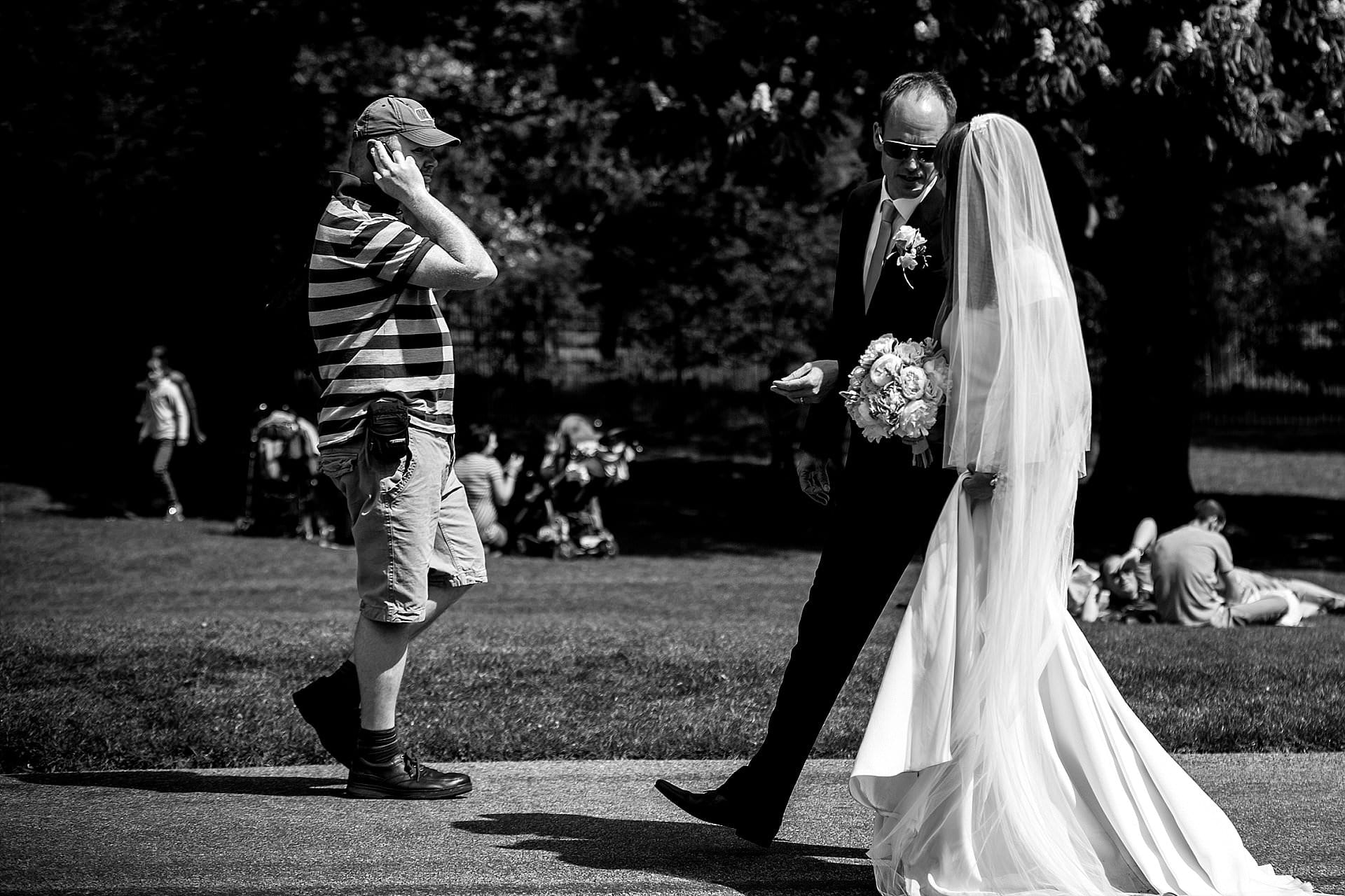 Newly married couple walk along a busy Windsor Long Walk