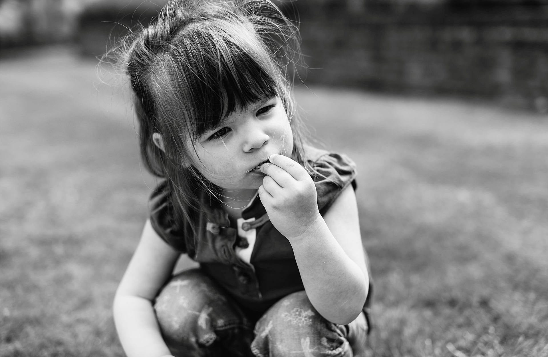 Girl eating some grass looking thoughtful