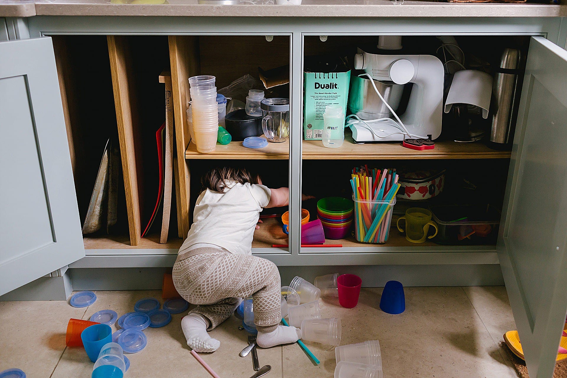 Toddler climbs into cupboard pulling things out