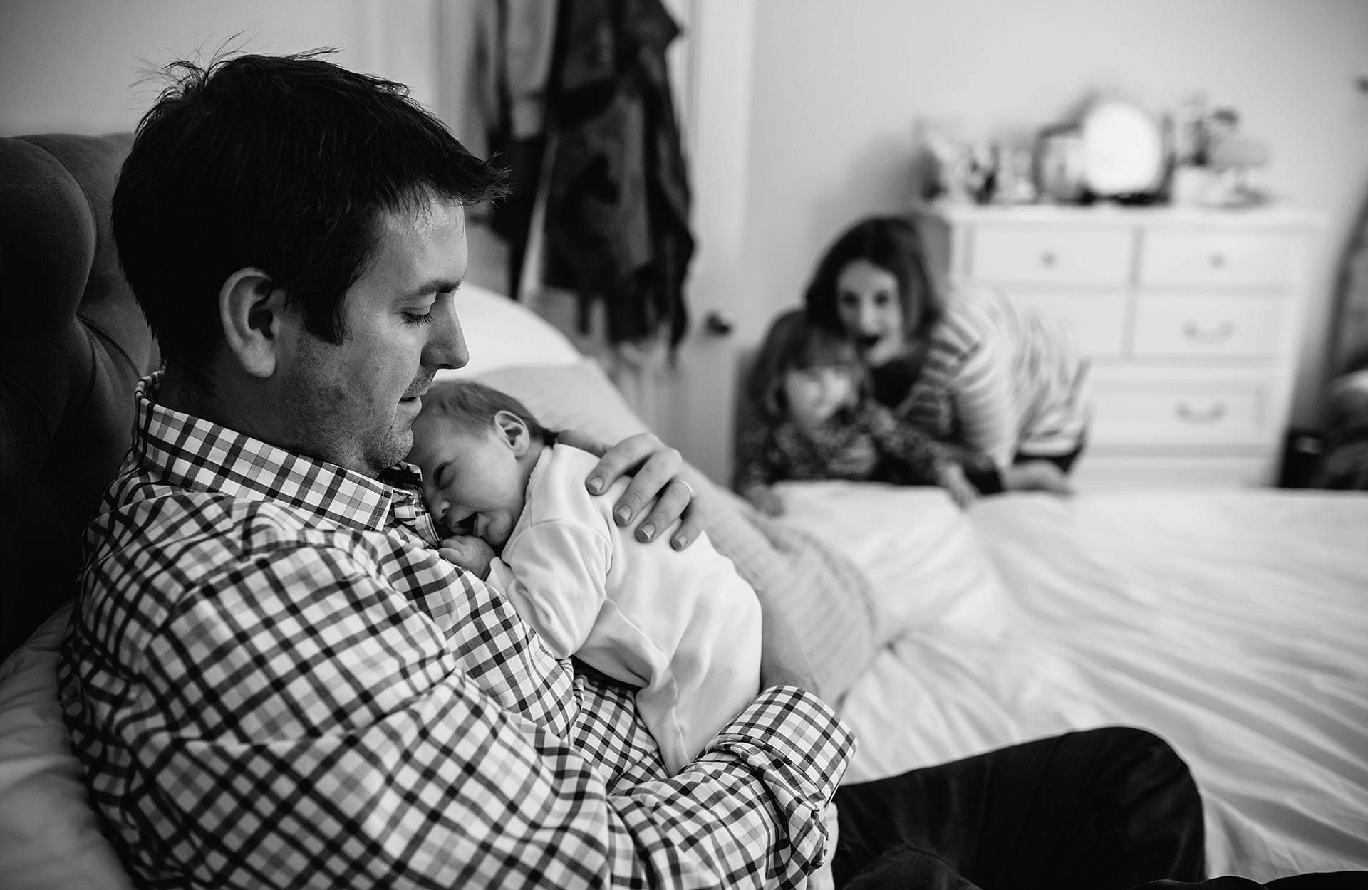 dad and baby sleeping on bed - with mum and daughter approaching