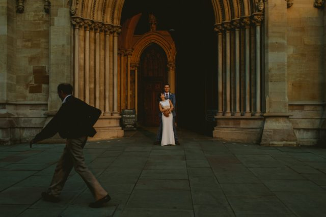 Man walking past while wedding couple pose for photos