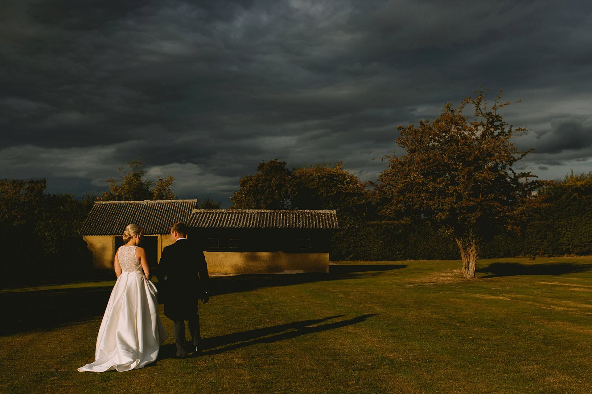 Bride and groom walk away with dark rain clouds above