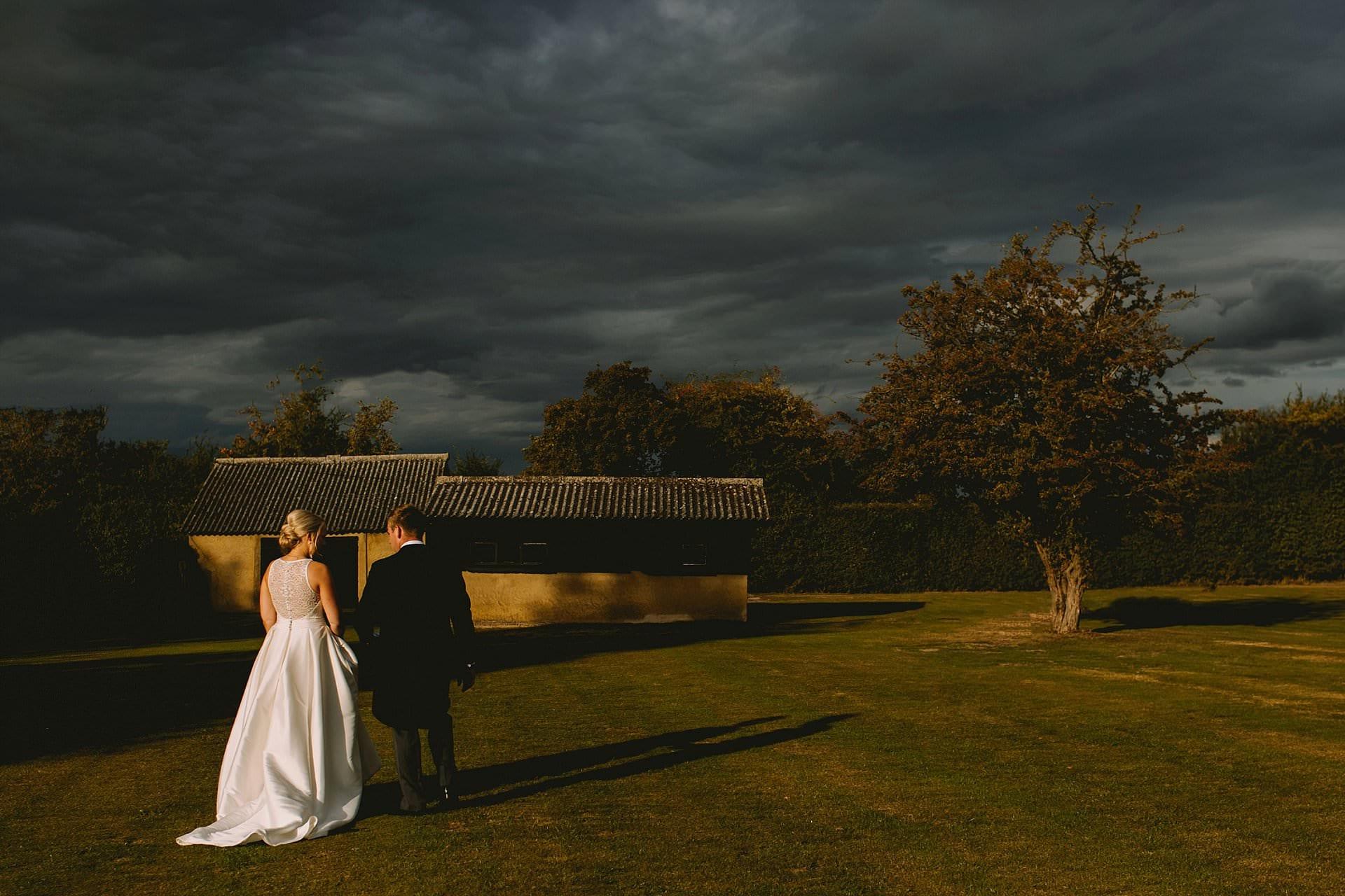 Bride and groom walk away with dark rain clouds above