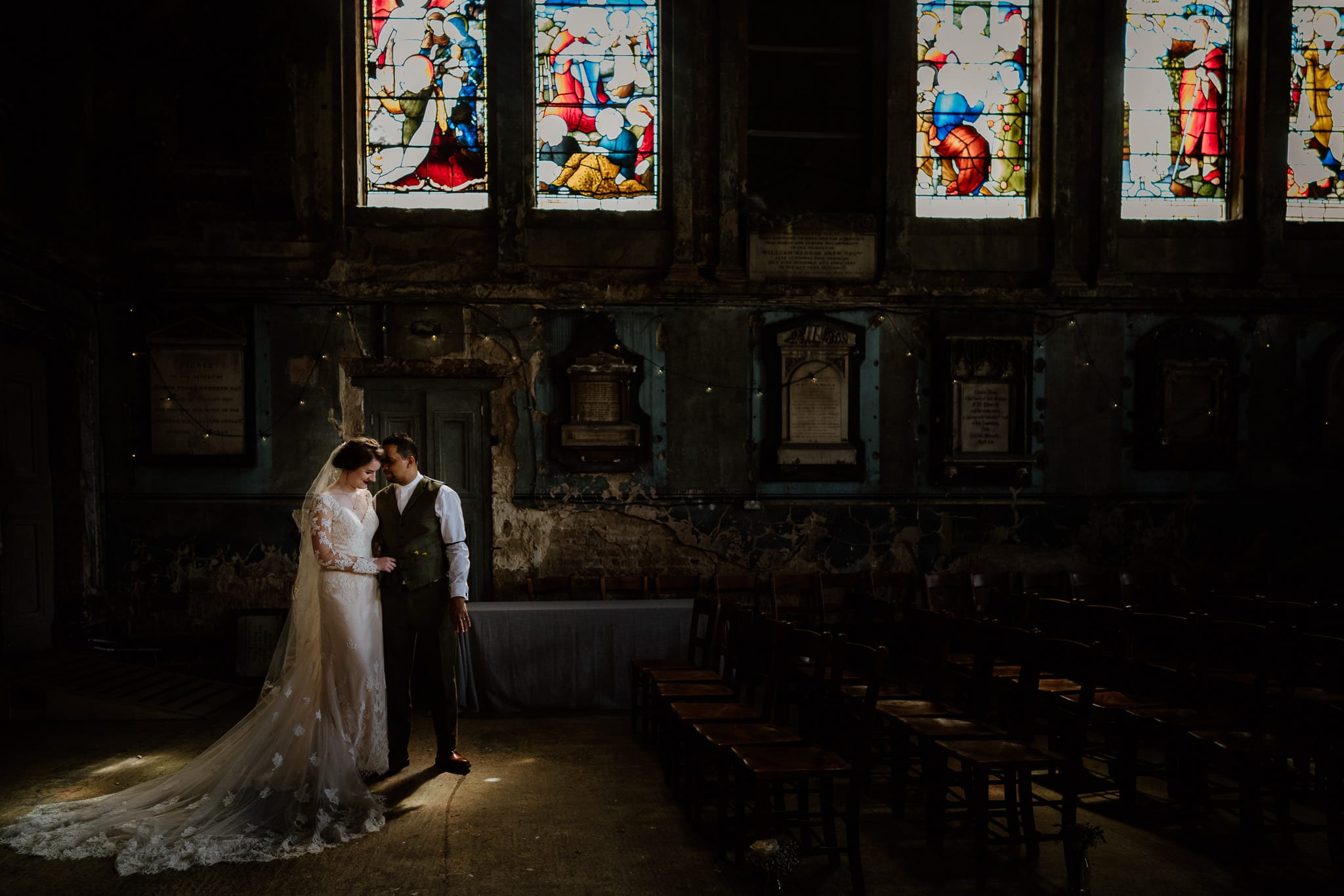 Couple pose in some pretty light in a chapel
