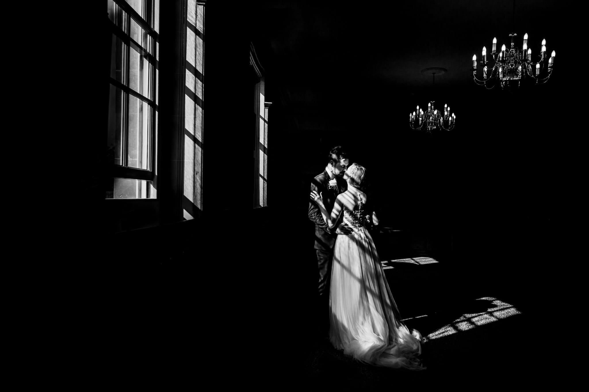 Light through a wedding hits couple having a kiss