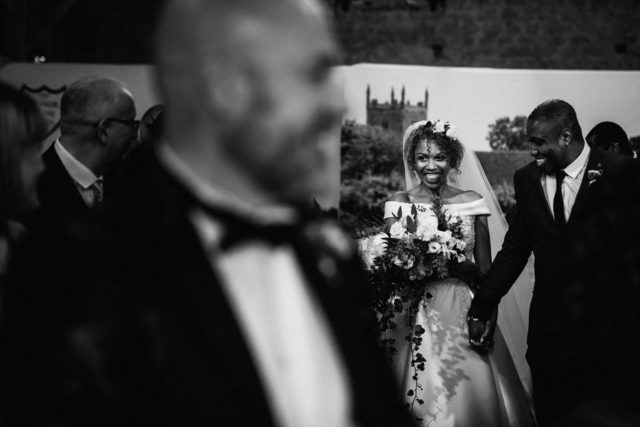 Bride walking down the aisle with her brother at Manor farm Barn Wedding Photography