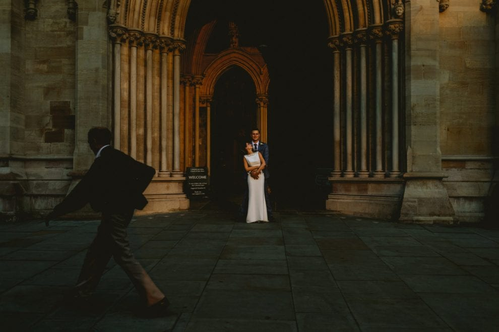 Man walks past as couple pose for photos outside St Albans Cathedral