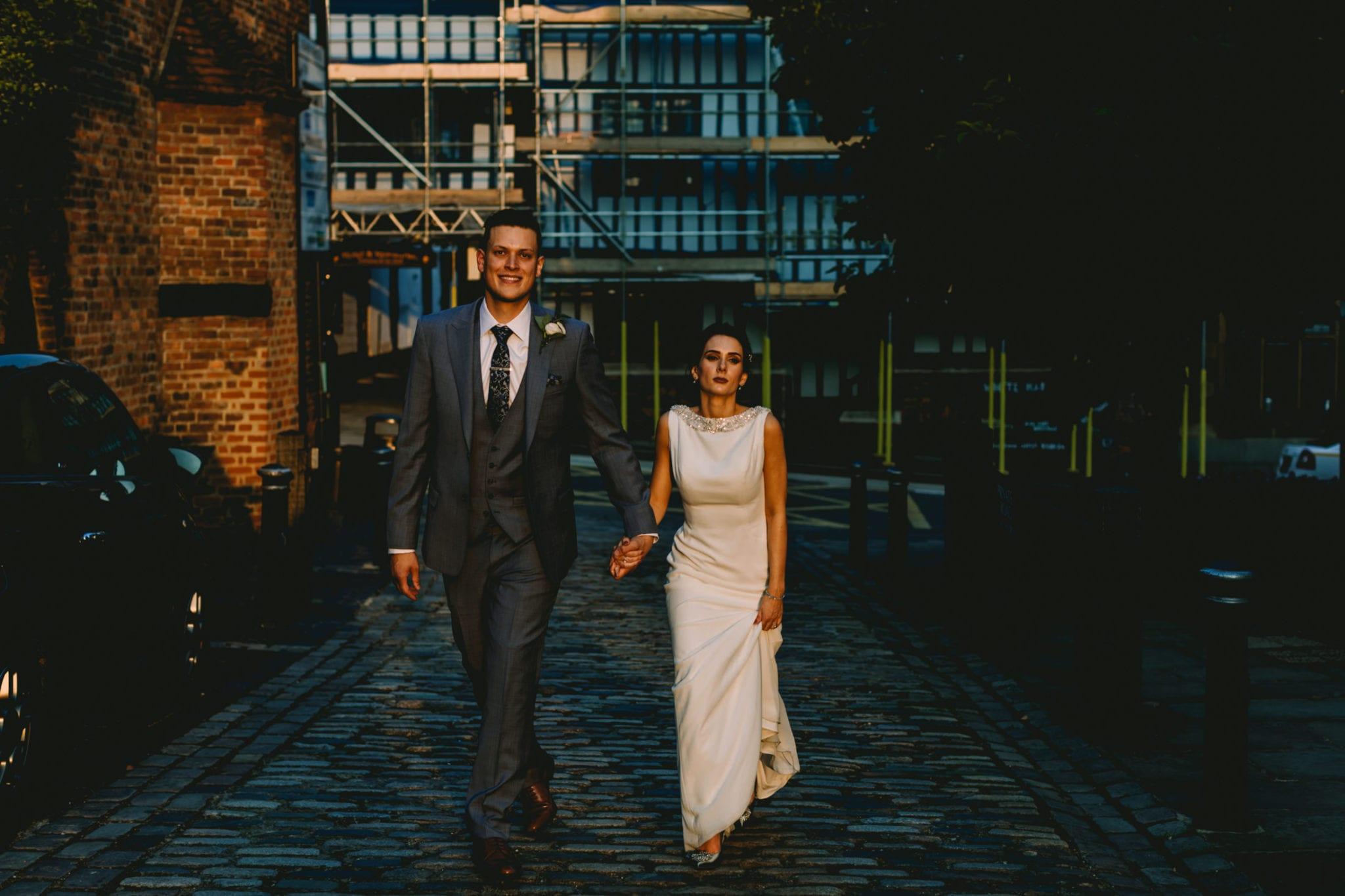 Bride and groom walk in the street in golden hour