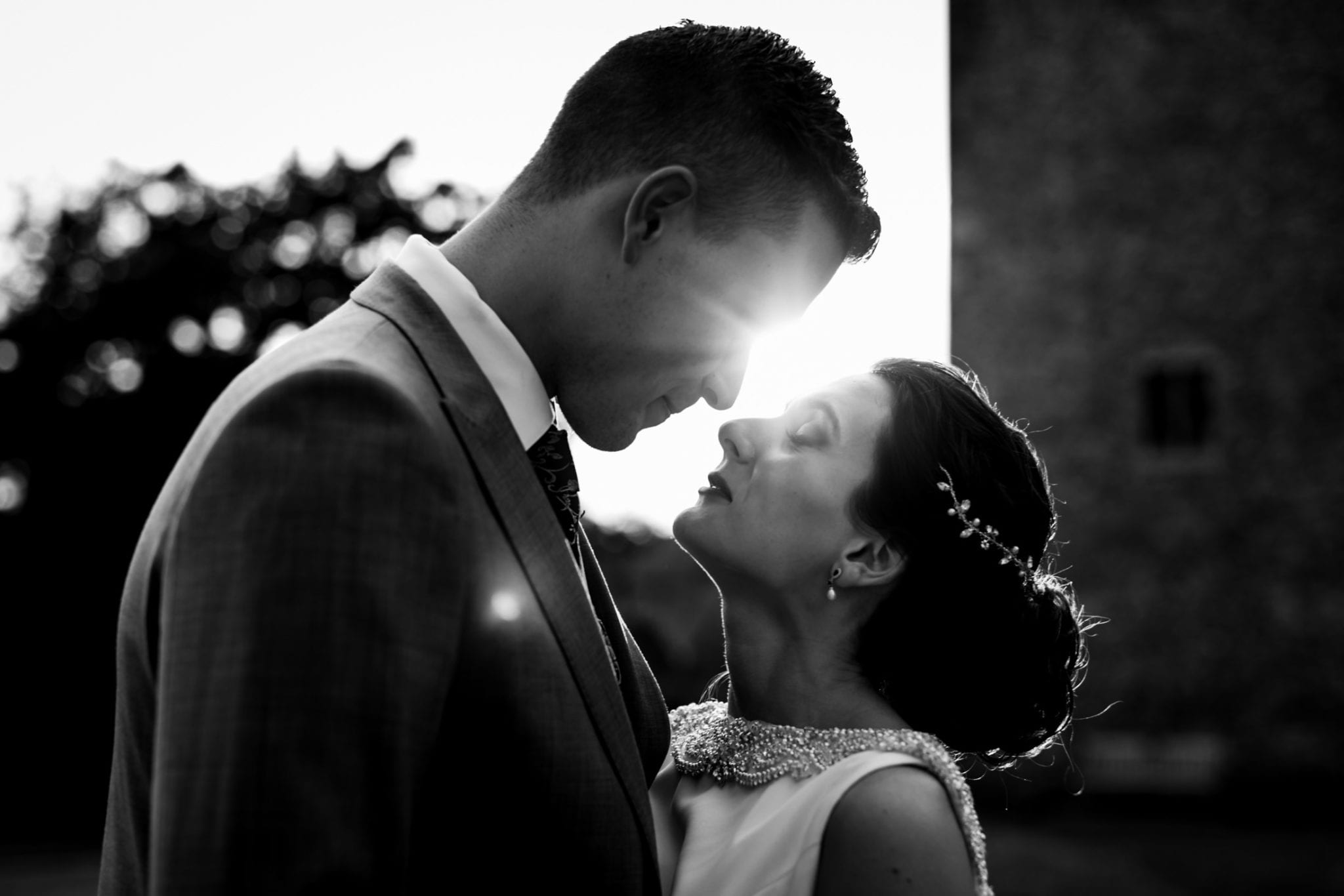 Couple pose in the sunshine for a wedding photo