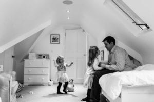 Daughters and dad in their bedroom playing
