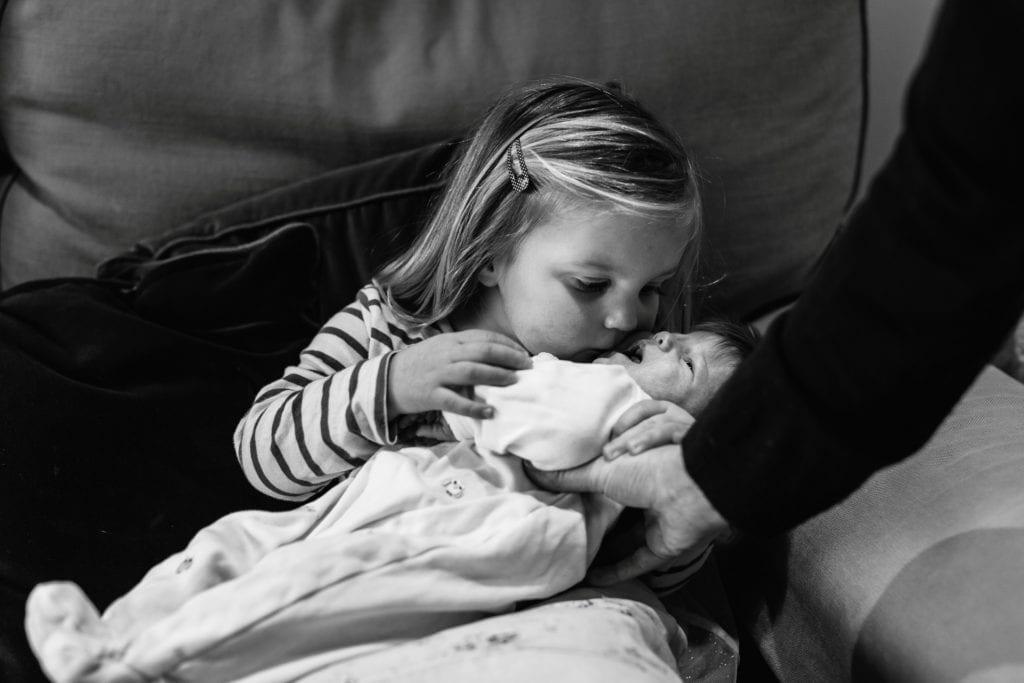 Little girl kisses her new baby sister