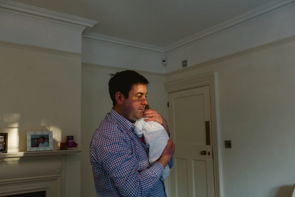 Dad holding baby in lovely window light