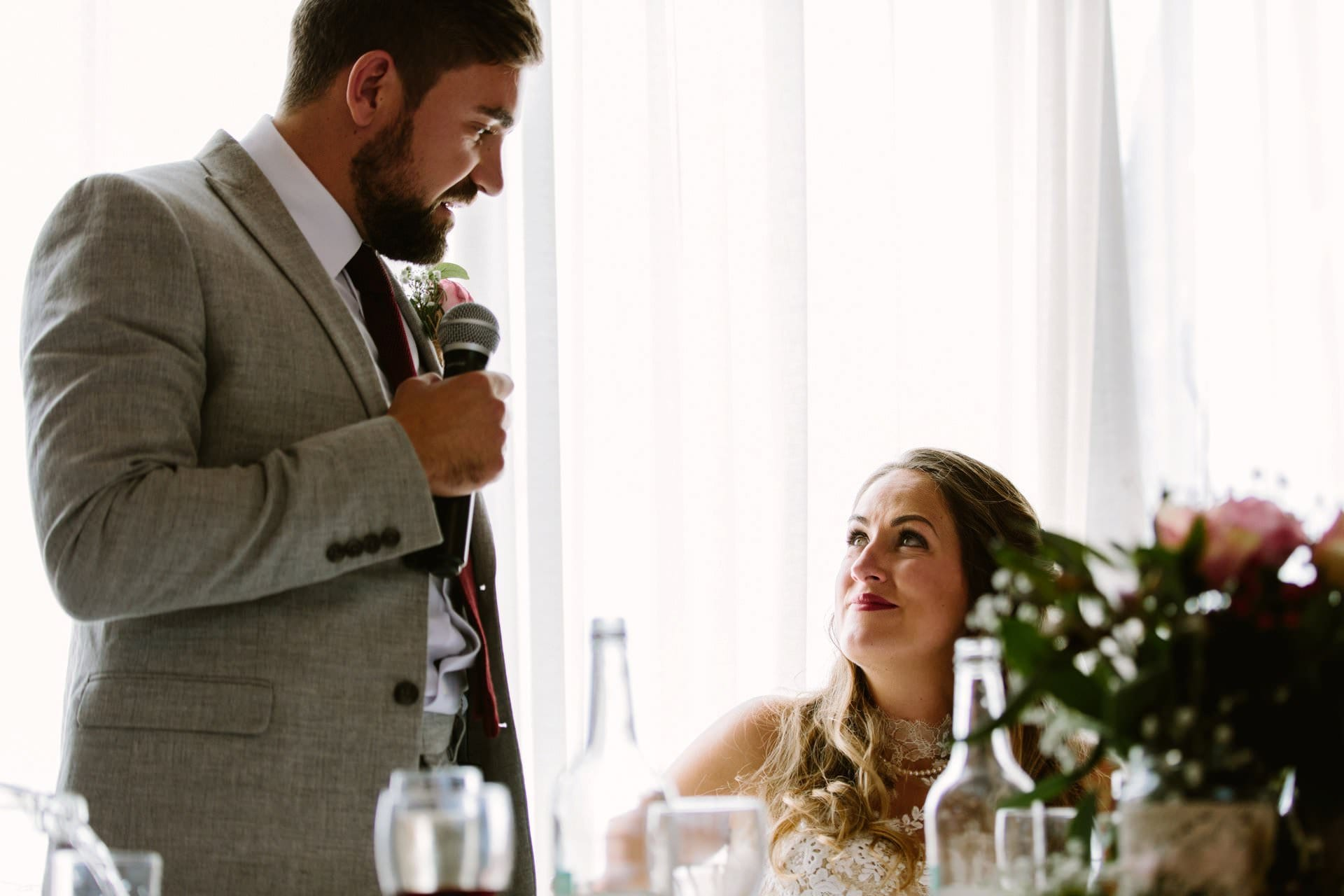 Bride looks at groom during his speech to her