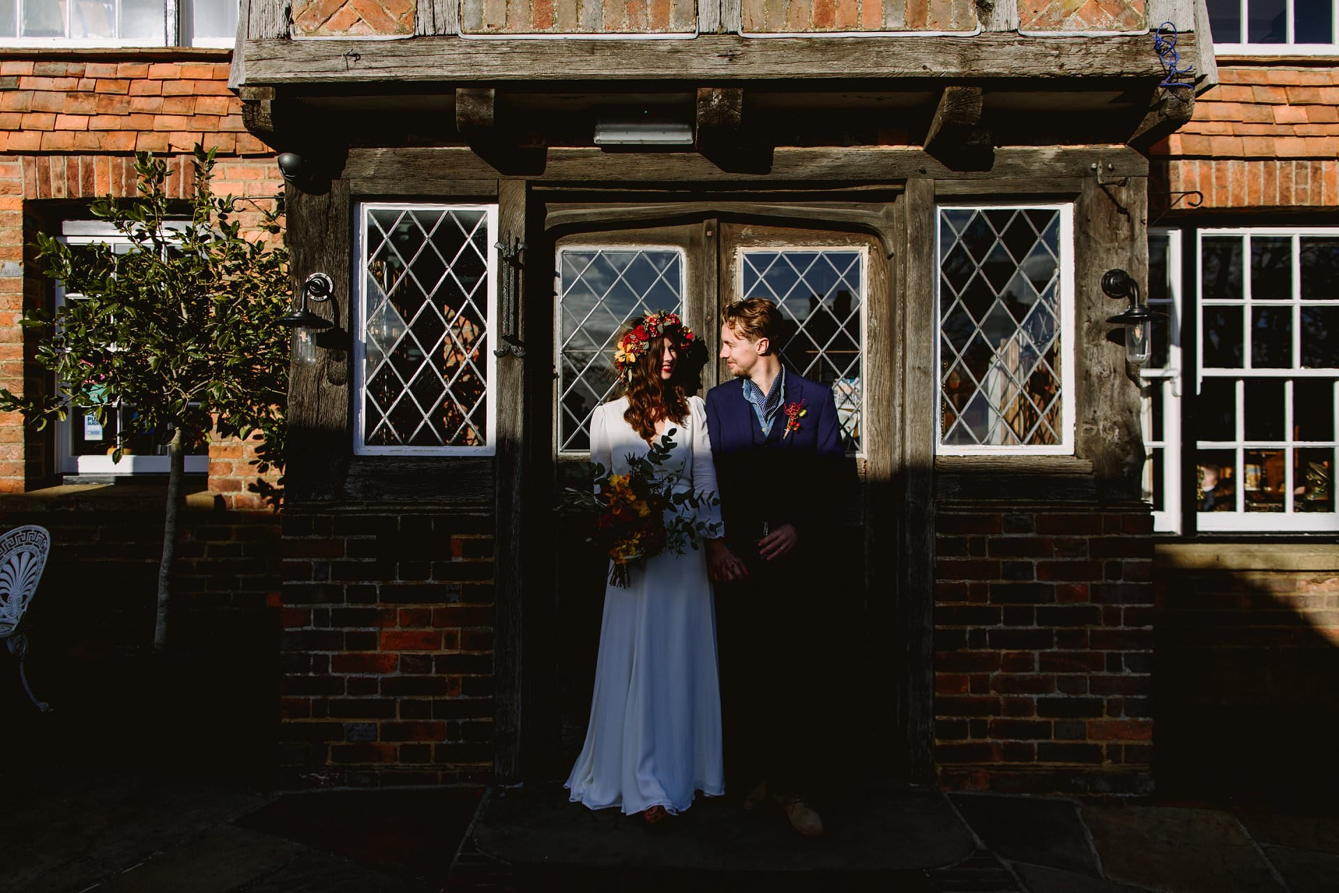 Couple in the sunshine against a wooden door