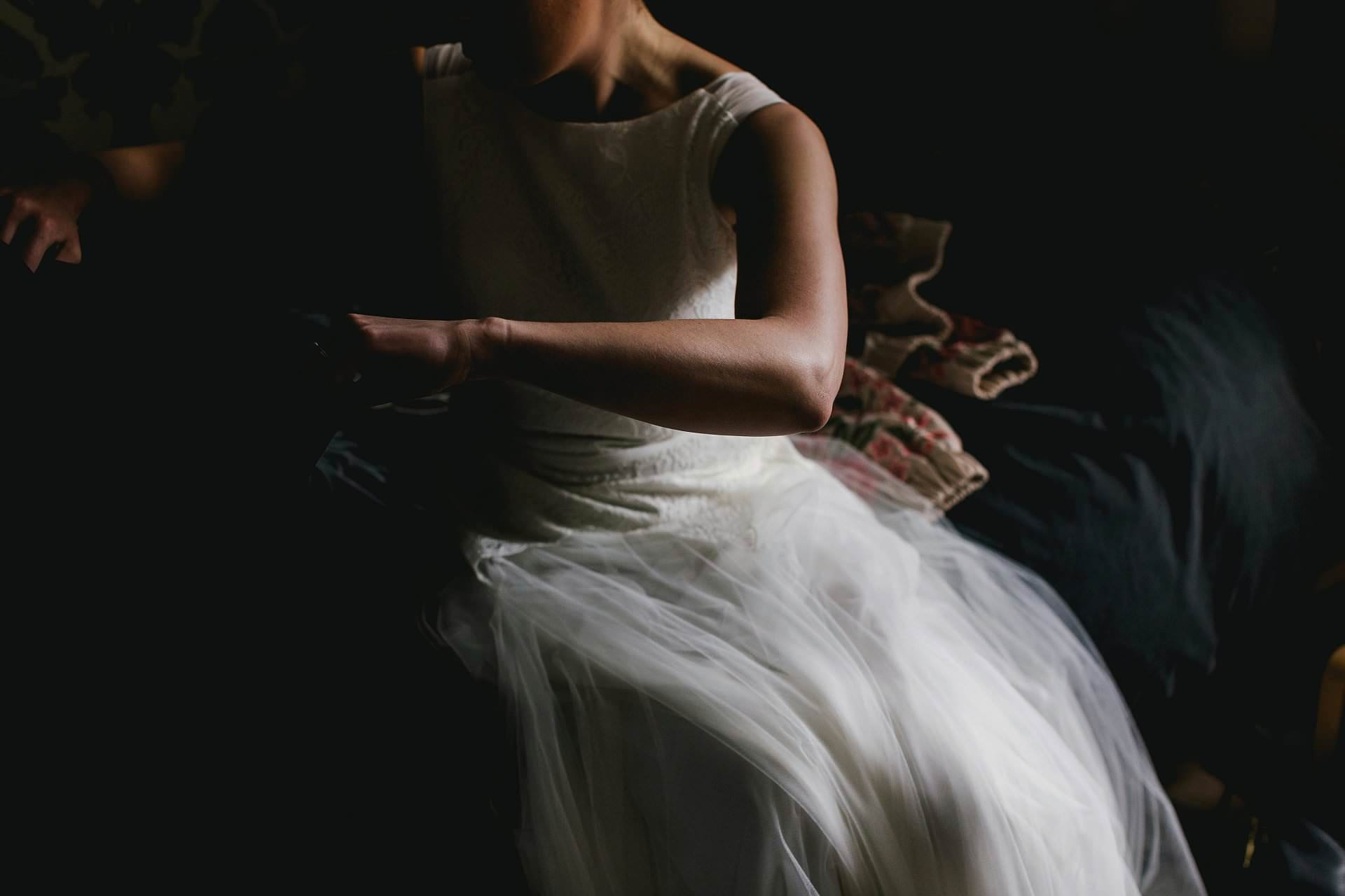 Light on brides arm and wedding dress