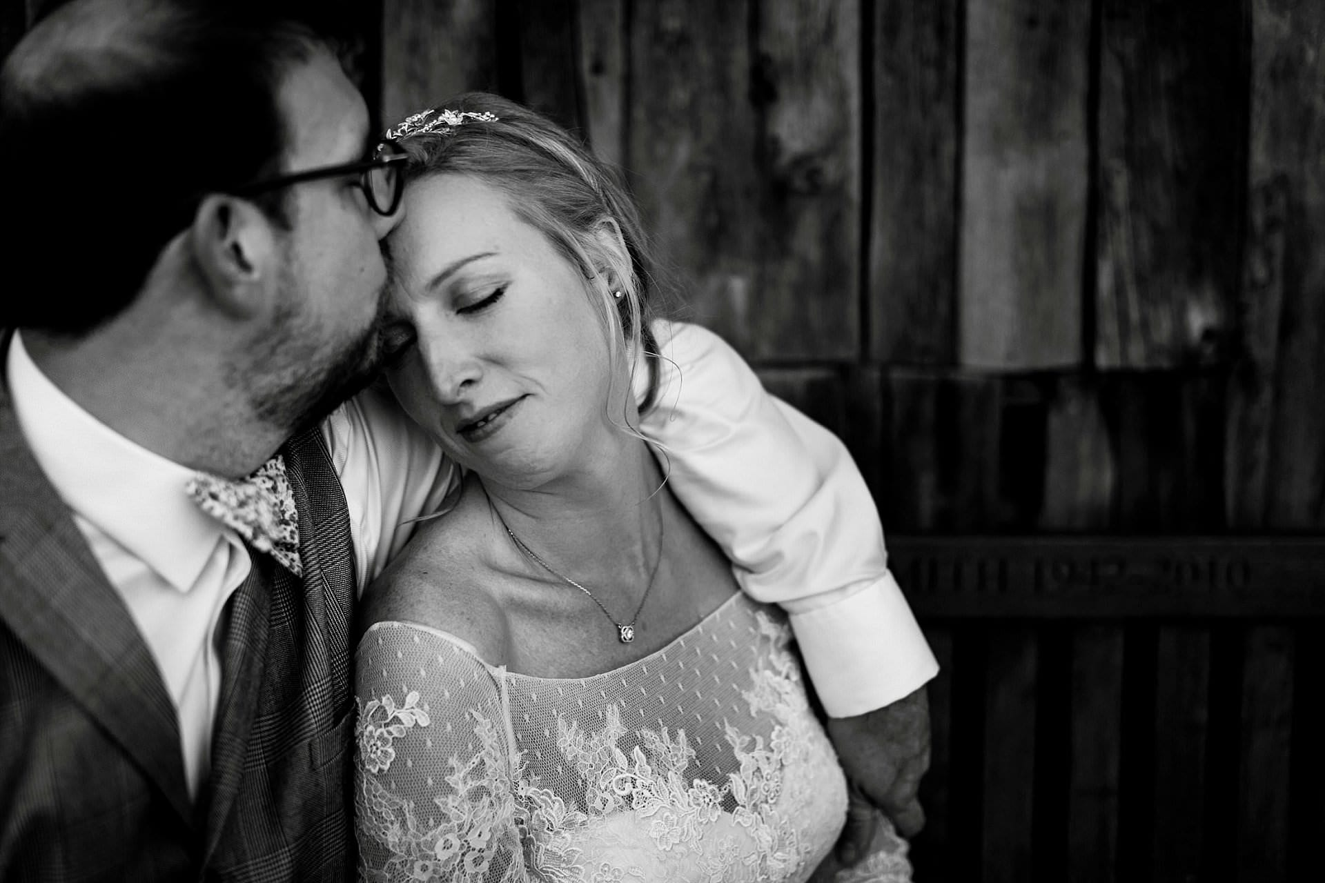 Groom kisses bride on the head with eyes closed