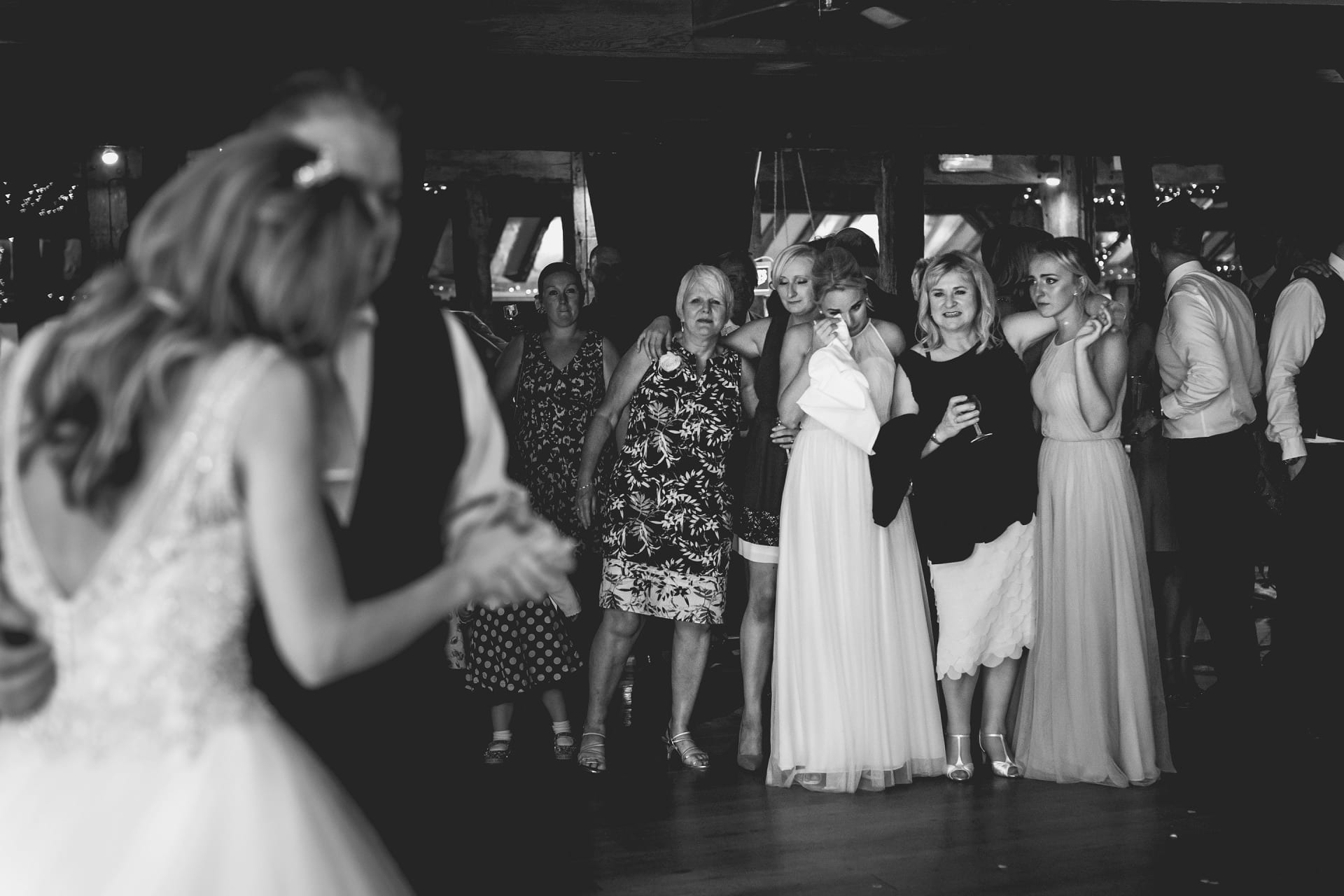 Mum and sister watching dad and daughter first dance