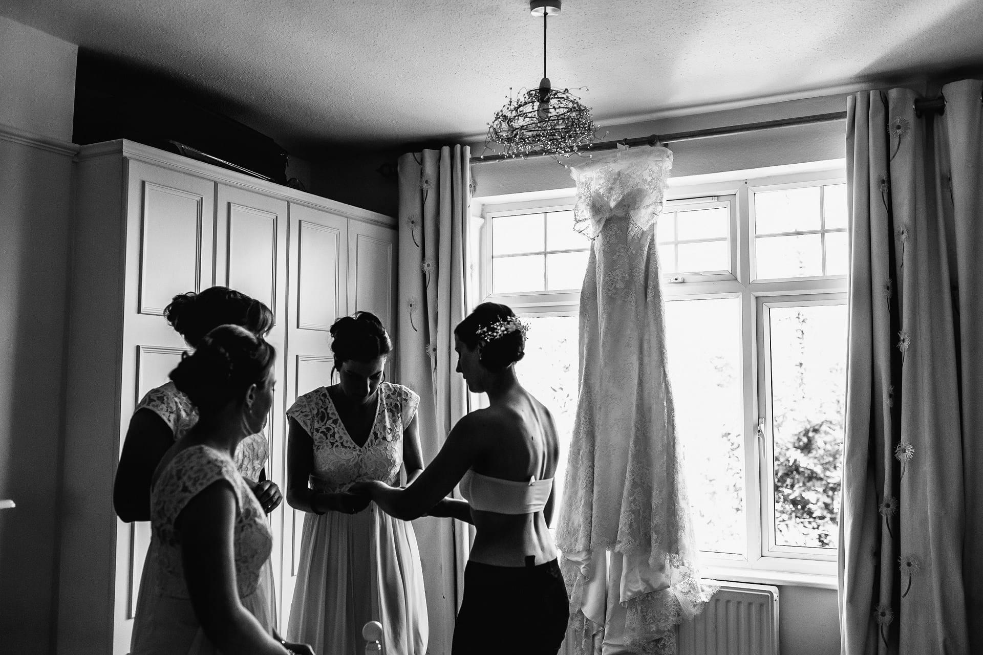 Bridesmaids help bride get ready before her wedding