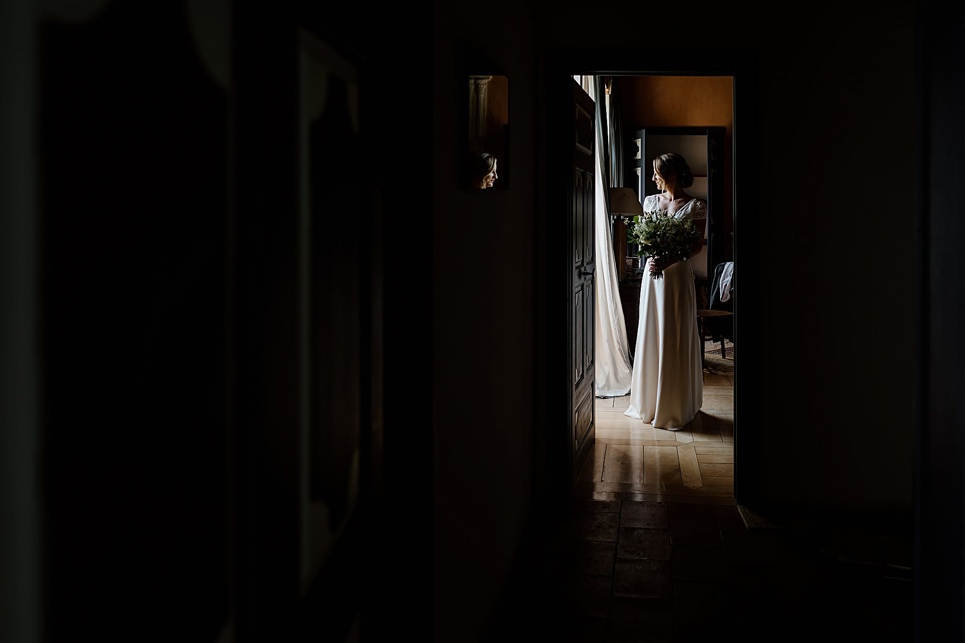 Bride standing in window light at a French Chateau