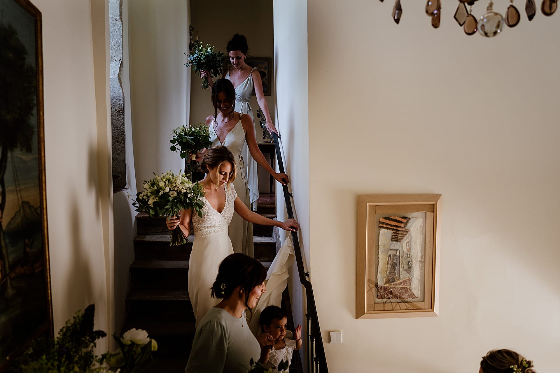 Bride and her maids walk down stairs for a French wedding