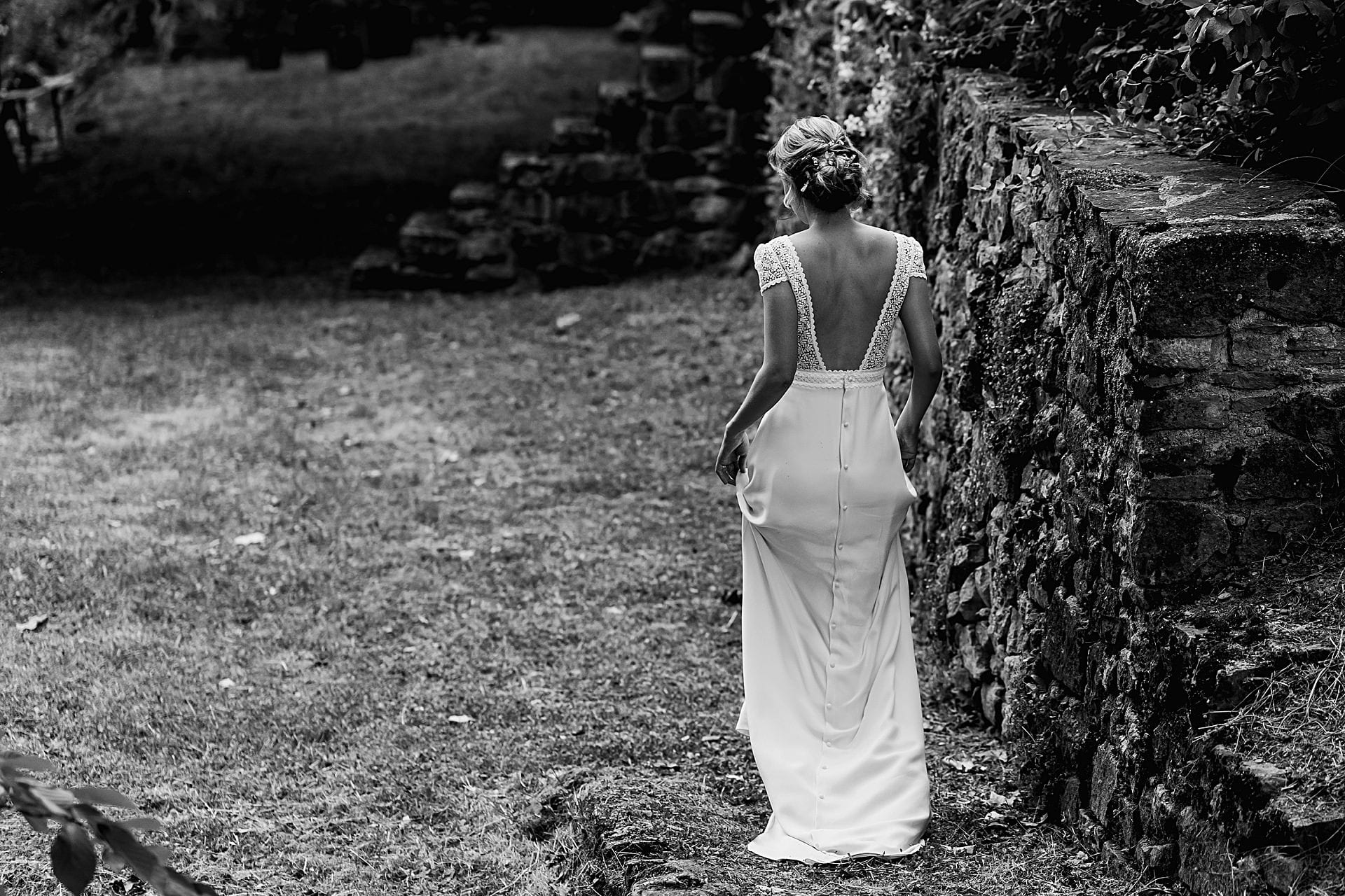 Bride holds her dress and walks towards guests