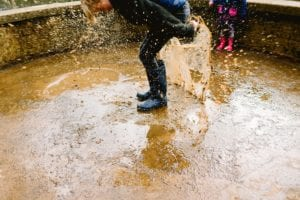 Boy splashes in a muddy puddle