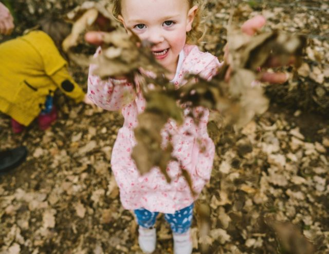 Little girl throws autumn leaves at the camera