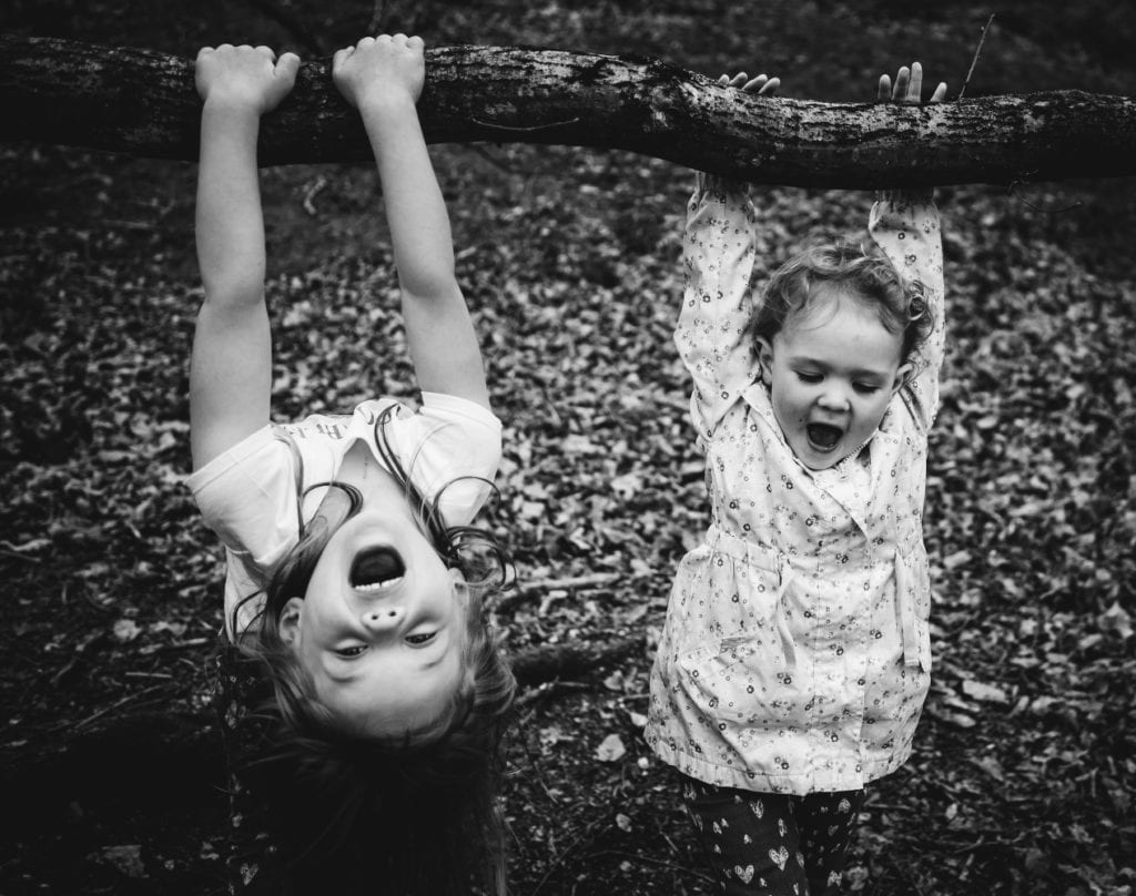 2 girls hanging off trees in the woods