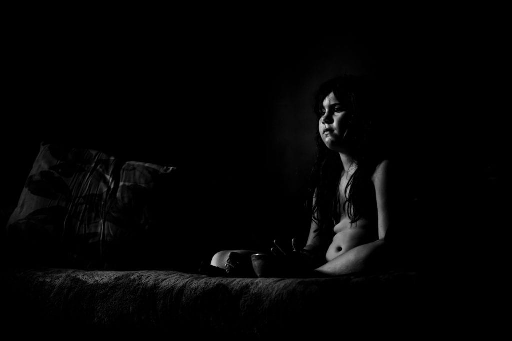 Girl on the sofa watching TV - black and white