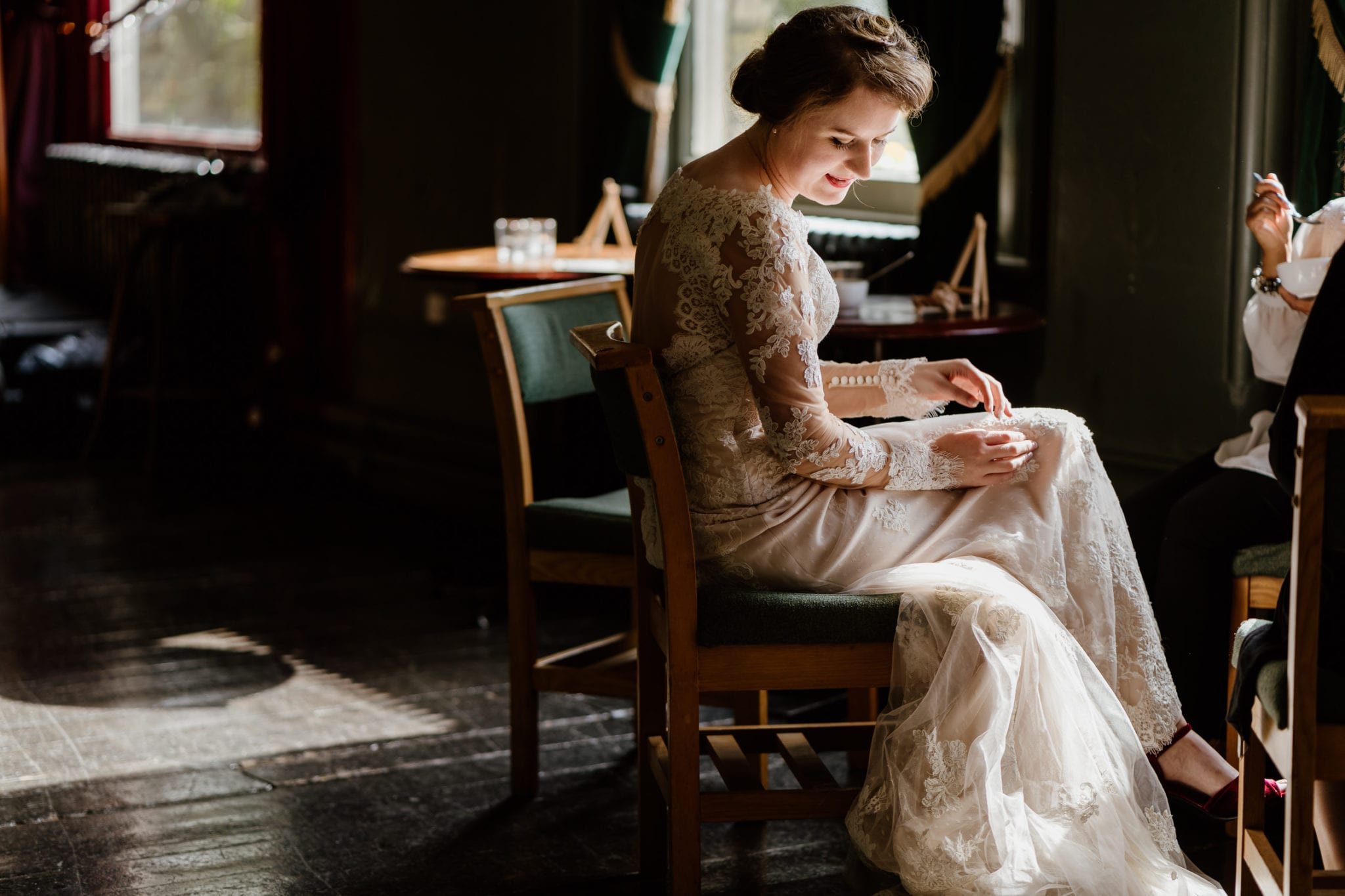 Bride sits in a chair bathed in window light