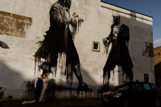 Bride and groom pose under London graffiti in East Dulwich