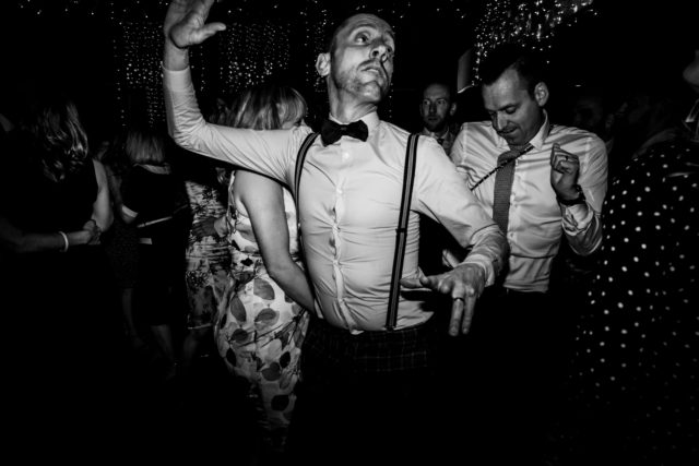 Man dancing at wedding in black and white
