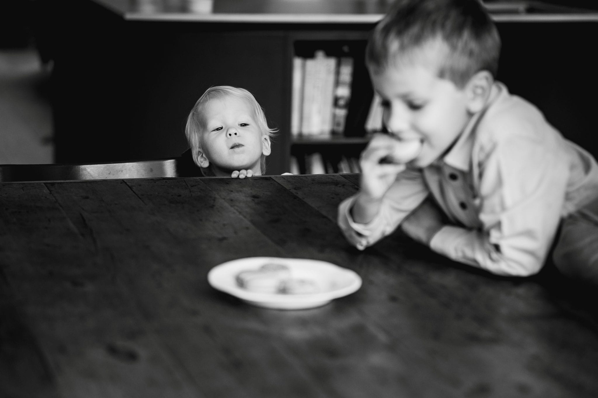 family Life Session - Little boy looking over the table at a biscuit