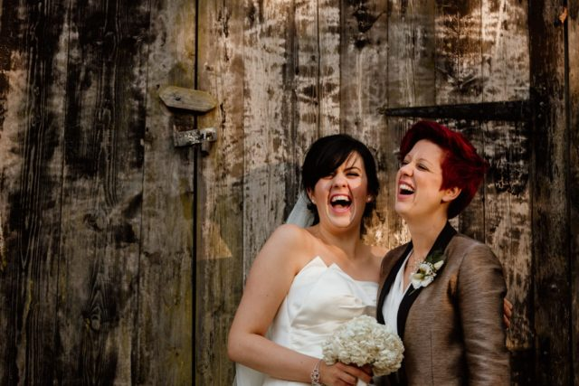 Two brides laughing at wedding